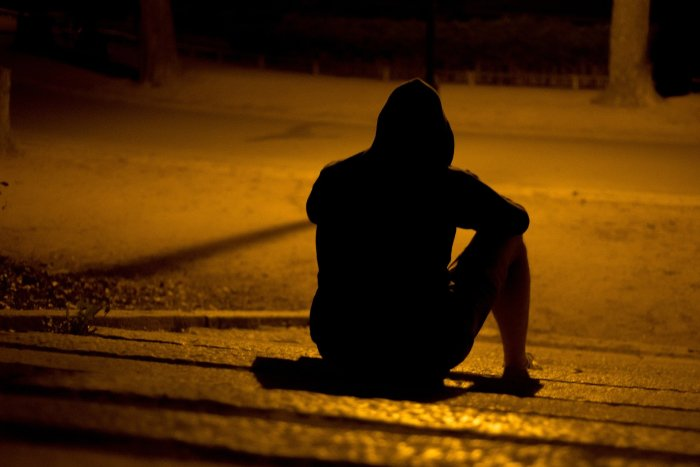 A lone figure sits in the shadows beneath a streetlight.
