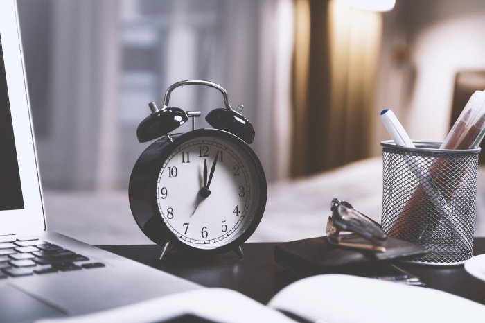 A black alarm clock sits on a desk next to a laptop.