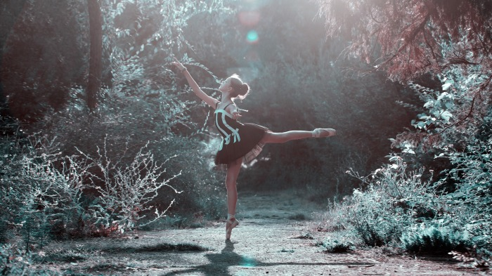A ballet dancer strikes a poised and delicate pose, showing mastery of her art.