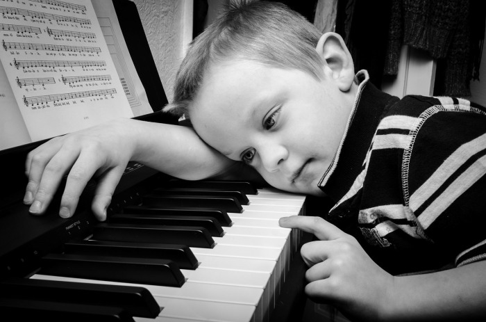 A boy slouches at a piano, showing disinterest in piano practice.