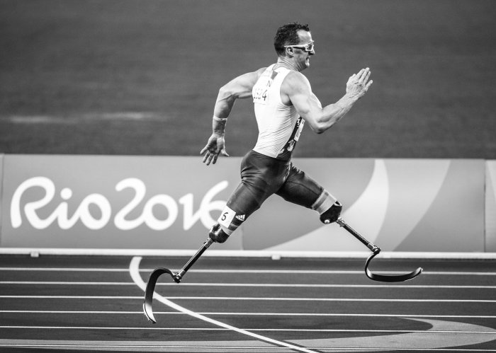 A black and white photo of a double amputee sprinting in the 2016 Rio Paralympics.
