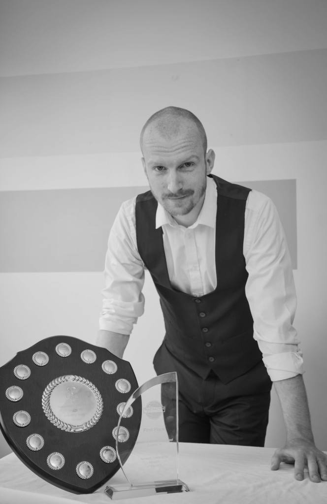 Simon Day, communications coach and founder of Simon Speaks, stands beside his award for becoming a 2019 UK Champion of Public Speaking.