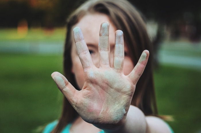A woman holds her hand in from of the camera in a 'stop' motion.