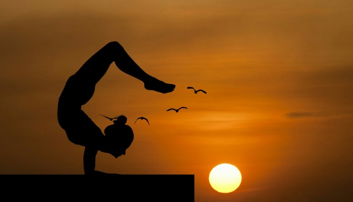 A woman strikes a yoga pose on the beach at sunset.